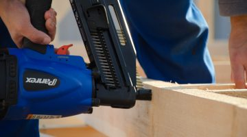 a person using a nail gun on a wood frame