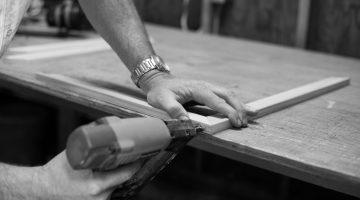 Person nailing a wood using nail gun